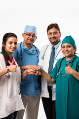 Group of successful Indian medical doctors, male and female standing isolated with thumbs up sign on white background, selective focus
