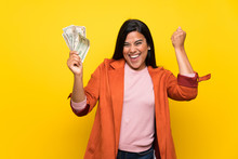 Young Colombian Girl Over Yellow Wall Taking A Lot Of Money