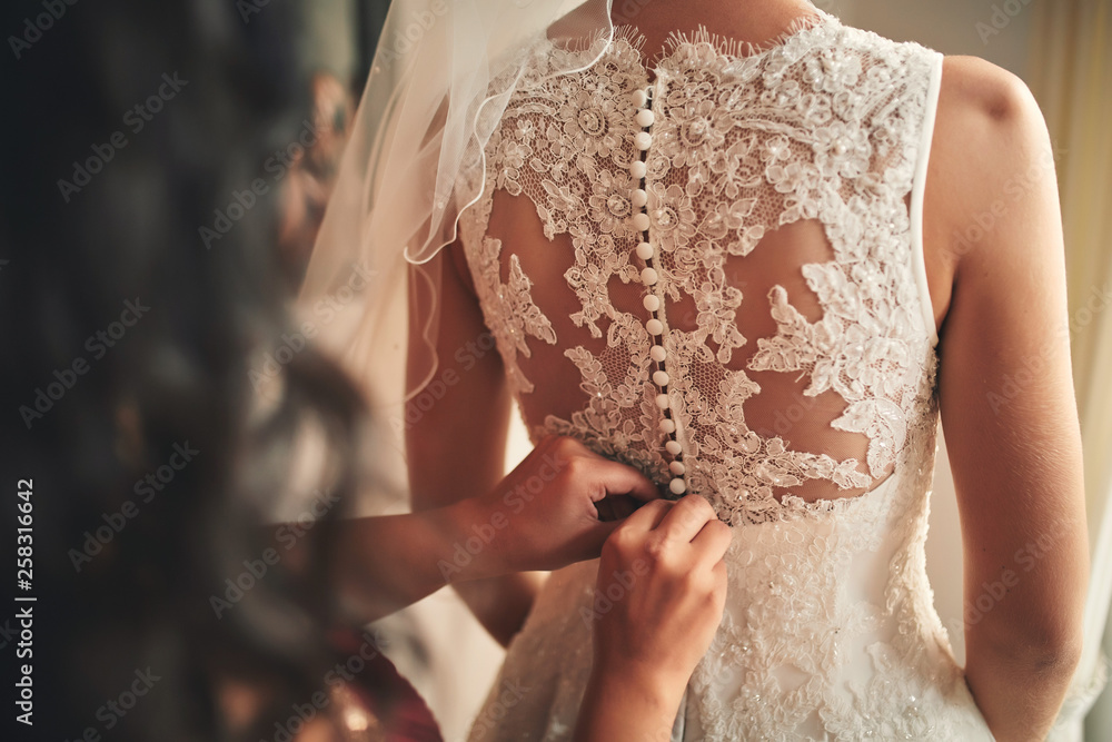 Fototapety, obrazy: Bridesmaid helping bride fasten corset close-up and getting her dress, preparation concept in morning for wedding day.