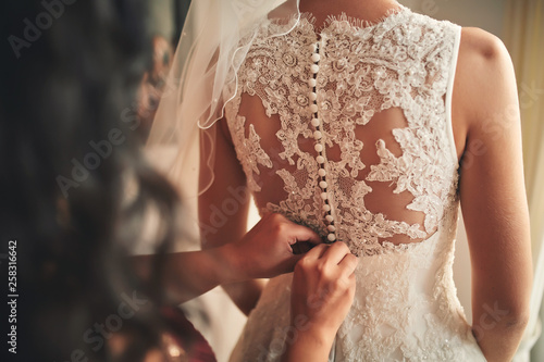 Fotografia  Bridesmaid helping bride fasten corset close-up and getting her dress, preparation concept in morning for wedding day