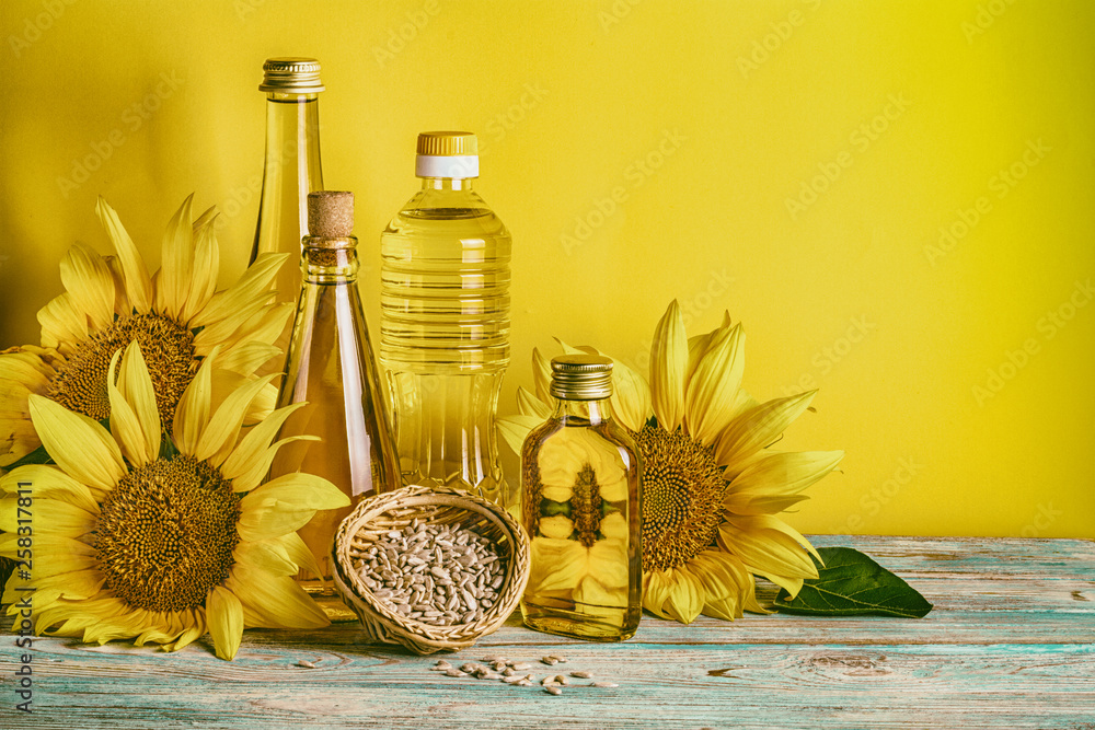 Fototapety, obrazy: Rural still-life - sunflower oil in bottles with flowers of sunflower (Helianthus annuus), closeup