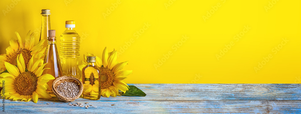 Fototapety, obrazy: Rural still-life, banner - sunflower oil in bottles with flowers of sunflower (Helianthus annuus), closeup with space for text