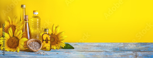 Poster Tournesol Rural still-life, banner - sunflower oil in bottles with flowers of sunflower (Helianthus annuus), closeup with space for text