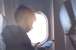 Caucasian boy fasten seat belt and using tablet pc during air flight. Safety travel with kid. concept