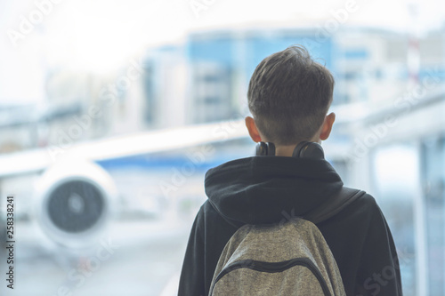 Fotografia, Obraz  A boy in headphones with a backpack stands near the window at the airport and looks at the plane