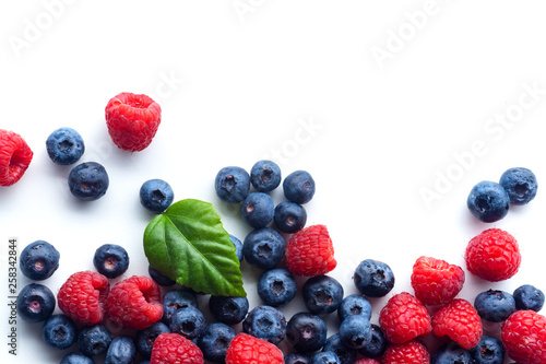Raspberries and blueberries isolated on white background with copy space - 258342844