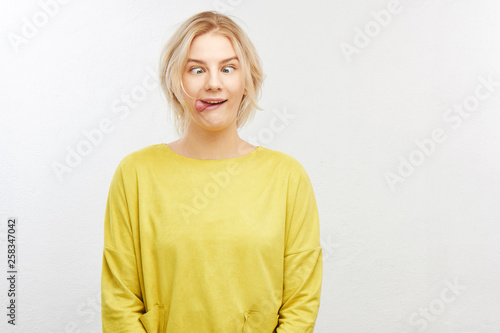 Photo A crazy blond girl in yellow clothes on white background squints eyes, sticks ou