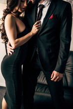 Cropped View Of Man In Suit Standing With Attractive Woman In Black Dress