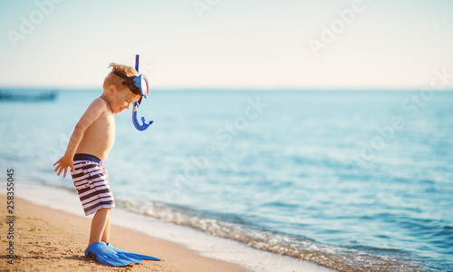 Photo  three years old boy playing at the beach with swimming ring