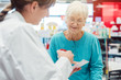 Ältere Frau in der Apotheke unterhält sich mit der Apothekerin