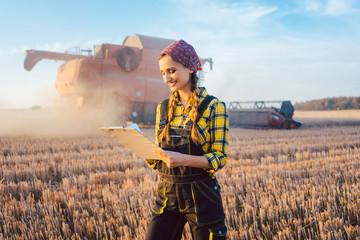 Bäuerin mit Clipboard auf dem Feld während der Ernte