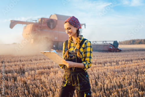 Fotografie, Obraz  Bäuerin mit Clipboard auf dem Feld während der Ernte