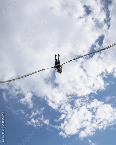 фотографія Girl hanging in slingshot against blue cloudy sky