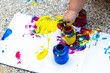 child hand draws a finger paint - blue, red and yellow on a white sheet of paper. Creative child development in kindergarten or free time at home