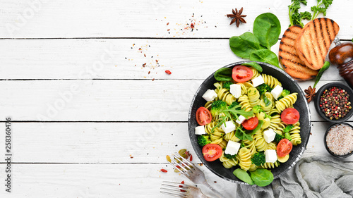 Pasta with spinach, tomatoes and feta cheese. In a black plate on a wooden background Top view. Free space for your text. Flat lay