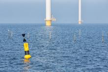Offshore Wind Turbines Near Dutch Coast With Buoy
