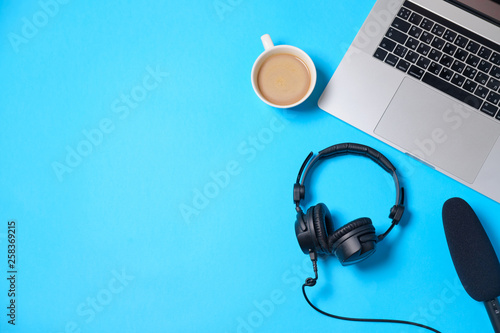 Music or podcast background with headphones, microphone, coffee and laptop on blue table, flat lay. Top view, flat lay - 258369215