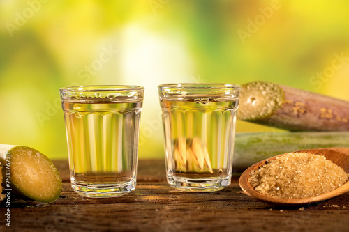 two shot glasses of Brazilian gold  cachaca with sugar and sugarcane isolated on Fototapet