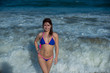 beautiful young woman in a seductive bikini comes out of the sea with high waves. Big waves in the ocean