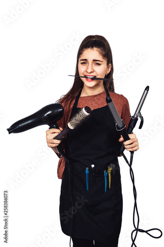 young girl hairdresser with a curling iron, hairdryer, comb in teeth.