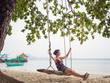 Caucasian woman is swinging on a wooden swing at the beach