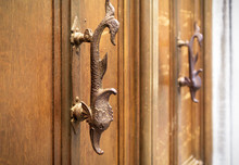 Old Wooden Door With Handles In The Form Of Fish, Venice, Italy. Ornate Vintage Entrance Door. Antique Artistic Knob Close-up. Unique Decorative Ancient Handle With Selected Focus.