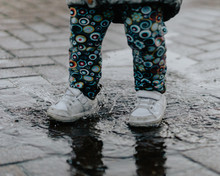 Toddler With White Shoes Running Through The Puddle On Cloudy Day In Residential Area.
