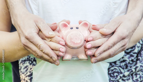 The child and parents are holding a piggy bank in their hands. Tableau sur Toile