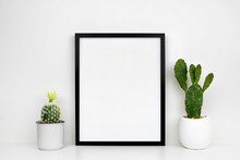 Mock Up Black Frame With Cactus Plants In Pots On A Shelf Or Desk. White Shelf And Wall. Portrait Frame Orientation.