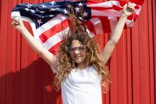 Portrait Of Smiling Girl Holding American Flag