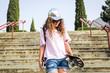 Girl with skateboard on steps