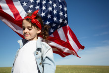 Girl With American Flag On Field In Remote Landscape