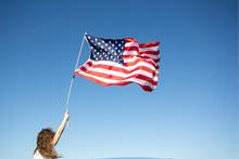 Girl Holding American Flag Under Blue Sky