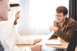 Arabian businessman signing cooperation agreement in office, another businessman submit documents. Arab business concept