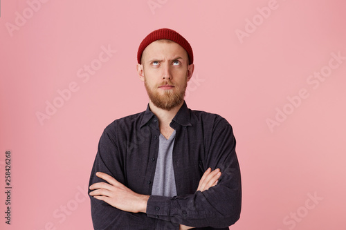 Fotografering  Photo of questioning bearded man in basic shirt, with red hat, with folded arms, look up with one raised eyebrow over pink background