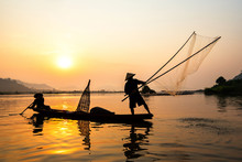 Asia Fisherman Net Using On Wooden Boat Casting Net Sunset Or Sunrise In The Mekong River - Silhouette Fisherman