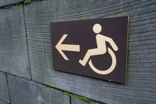 White And Grey Handicapped Wheelchair Access Sign Icon And Arrow On A Rough Textured Outdoor Wall With Moss