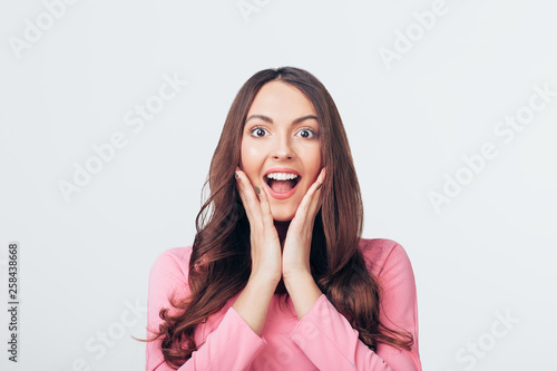 Fotografie, Tablou Young happy and surprised woman looking to camera and holds cheeks by hands isol