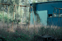 Abandoned Summer Campsite Turquoise Building With Swing In The Grass