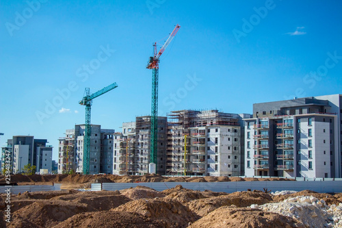 construction site with working cranes on blue sky background