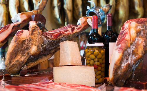Valokuva  Still life of spanish pork jammon on holder, bottles of wine cheese and olives