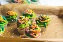 Beautiful, Bright, Very Colorful Muffins Decorated With Rainbow Cream And Candy Confetti, On A Bright, Spring Background