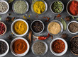 Various dry spices flat lay in small bowls on gray background. Top view,