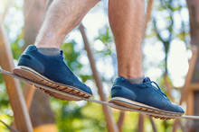 Closeup Male Legs In Blue Sneakers Walking And Keep Balance On Thin Ropes On High Trees In Park. Rope Park With Different Obstacles And Ziplines. Extreme Rest And Summer Activities Concept.