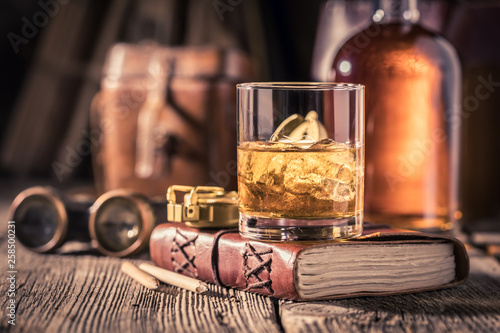 Photo Gold and cold whisky with ice and golden bottle