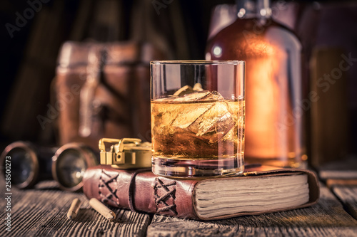 Closeup of whisky with ice on old journal Canvas Print