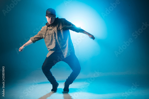 Valokuvatapetti Sporty modern style hip-hop dancer dressed in urban style wear shows his dance on blue studio background