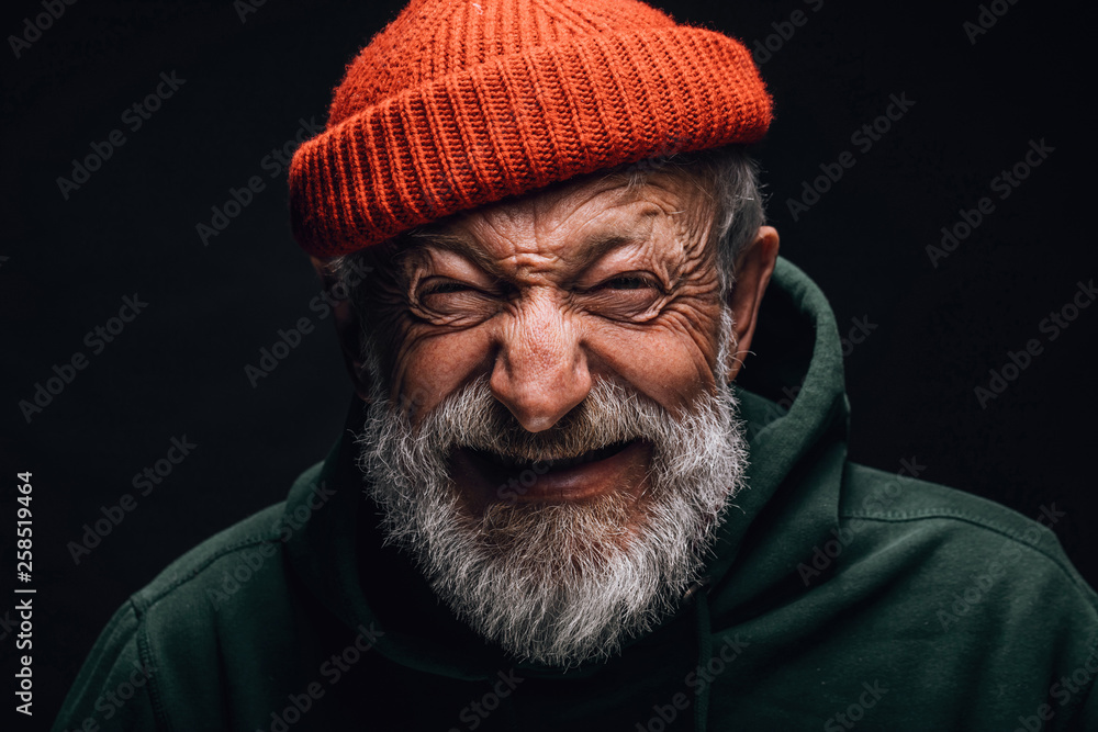 Fototapeta Grey- haired aged grandfather feeling overjoyed and excited while telling about his trip to mountains. Old man dressed in red knitted hat and green hoodie. Happy to be active in retirement