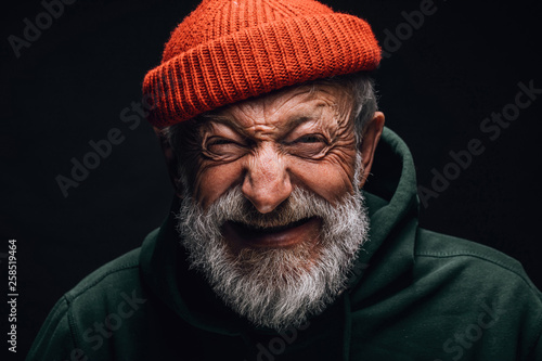 Obraz Grey- haired aged grandfather feeling overjoyed and excited while telling about his trip to mountains. Old man dressed in red knitted hat and green hoodie. Happy to be active in retirement - fototapety do salonu