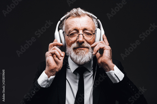 Studio isolated shot of handsome mature grey-haired businessman with headphones, listening songs loudly, relaxing and having a rest for his soul. People, leisure and modern technology concept. - 258519641